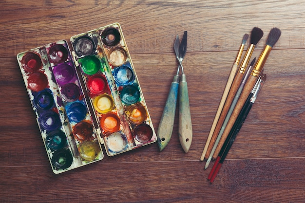 Paint brushes and watercolor on wooden table