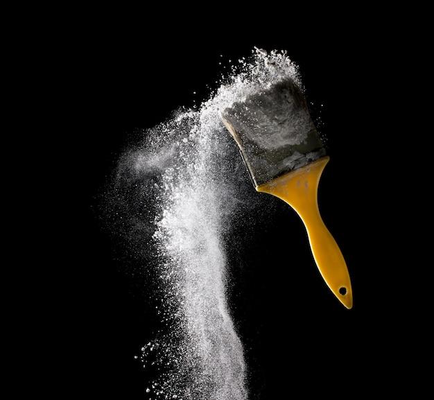 黒の背景に分離された抽象的な白い粉の爆発でペイントブラシ。