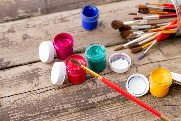 Paint brushes with gouache in bucket isolated on wooden