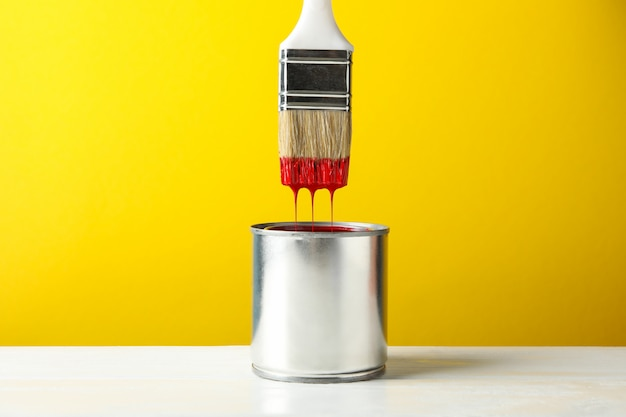Paint can and brush against yellow surface