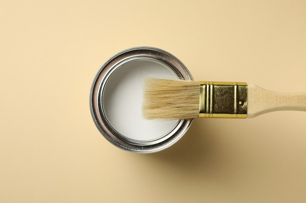 Paint can and brush on beige surface