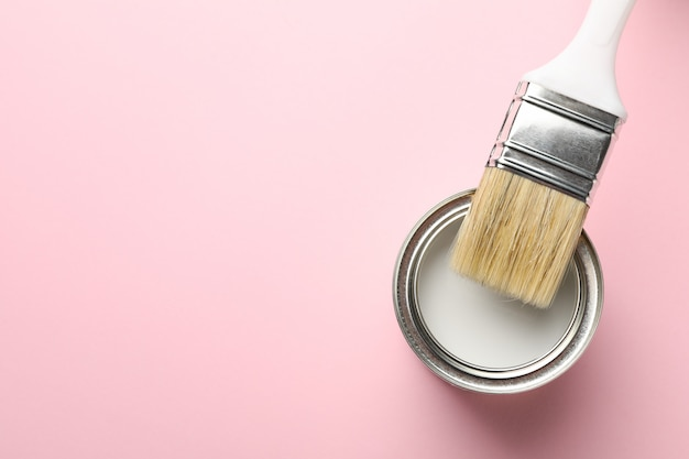 Paint can and brush on pink background, top view