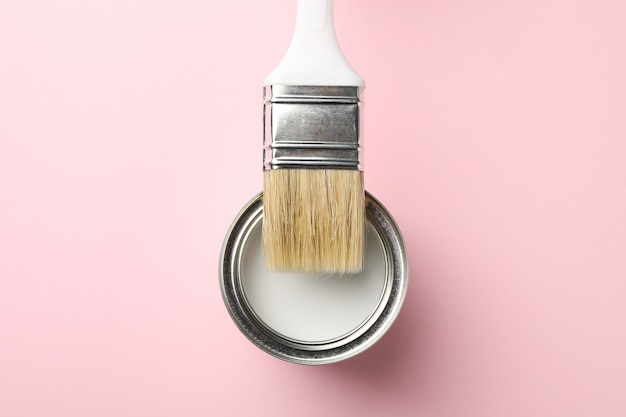 Paint can and brush on pink surface