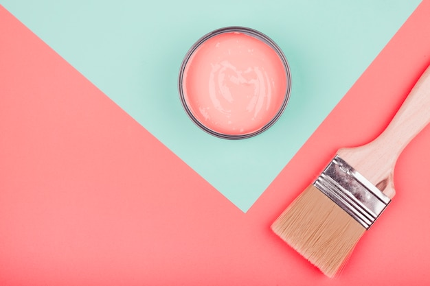 Paint can and paintbrush on mint and coral dual backdrop