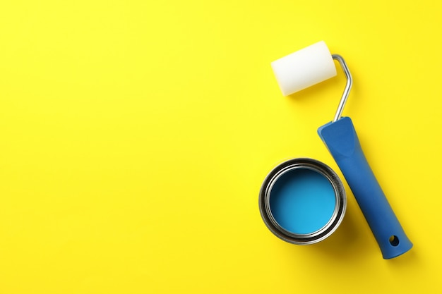 Paint can and roller on yellow background, top view