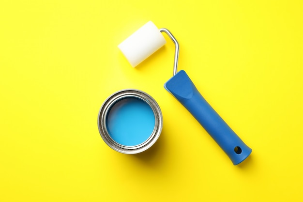 Paint can and roller on yellow surface