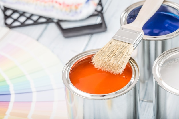 Кисть банки с краской и цветовая палитра на столе.