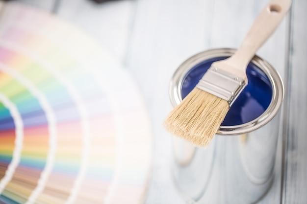 테이블에 페인트 캔 브러시와 색상 팔레트.