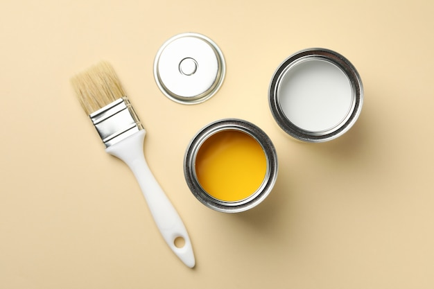 Paint cans and brush on beige background, top view