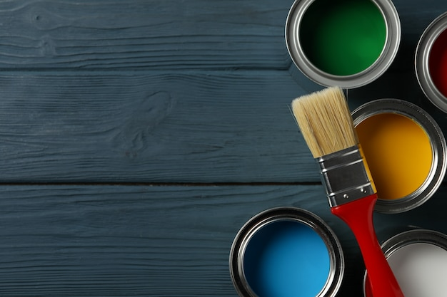 Paint cans and brush on wooden surface