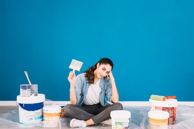 앉아있는 여자와 양동이와 페인트 개념