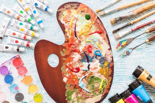 Dipingi la tavolozza circondata da materiale pittorico