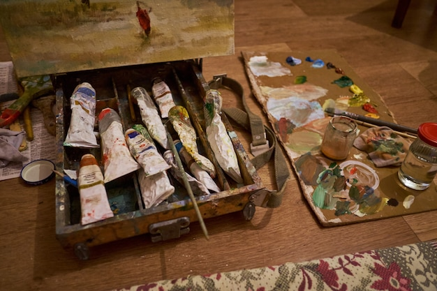 Paint palette with a brush in the box in the artist's studio