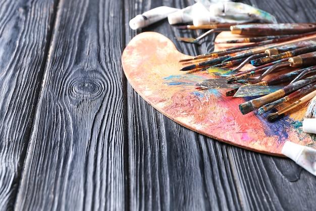 Палитра красок с принадлежностями на деревянном столе