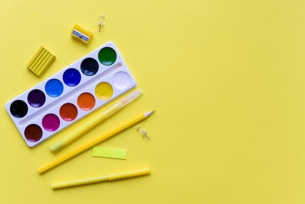 ペンキ、鉛筆、はさみ。黄色の背景に学校のアクセサリー。上からの眺め。