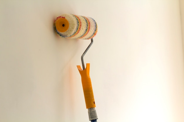 Paint roller brush near wall in renovated room interior isolated on white surface. renovation and diy concept.