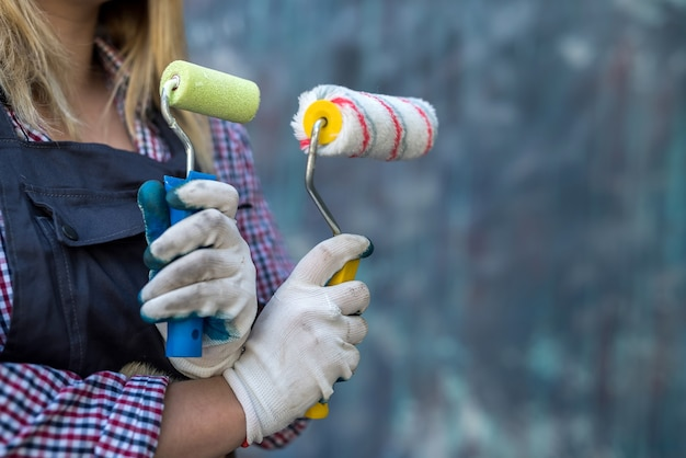 Paint roller in female hand near colorful wall. renovation