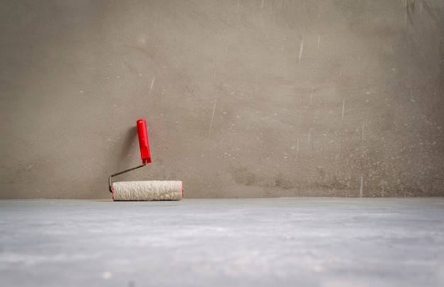시멘트 바닥에 빈 방에 페인트 롤러. 그런 지 인테리어 배경입니다.