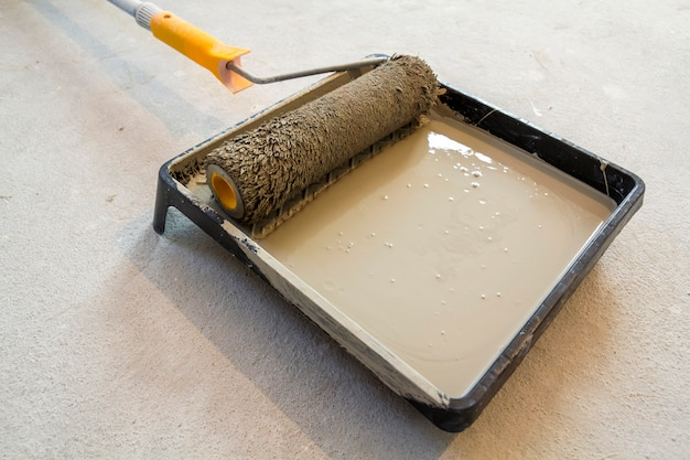 Paint roller in paint tray with grey color in the tray