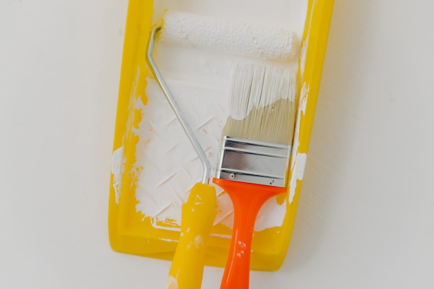 Paint roller and paintbrush in tray over white. refurbishment, repairing and decoration concept.