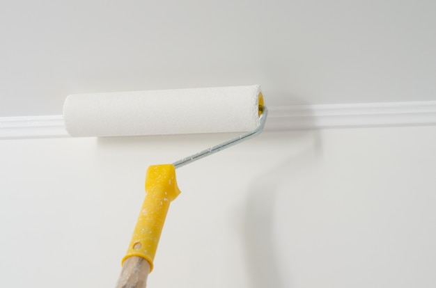 Paint roller with yellow handle. ceiling and wall painting process. white . copyspace