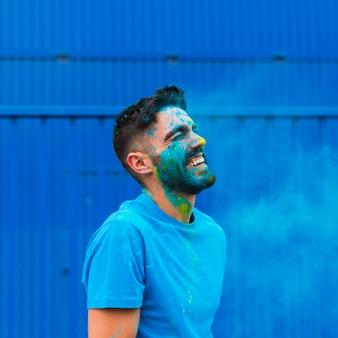 Краска запятнанного молодого человека смеется на фестивале холи