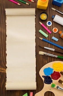 Paint supplies and brush on wooden table