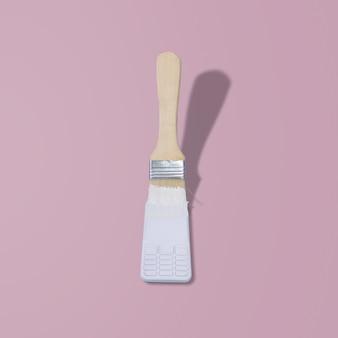 전화기를 흰색으로 칠하고 분홍색 배경에 붓을 칠하다