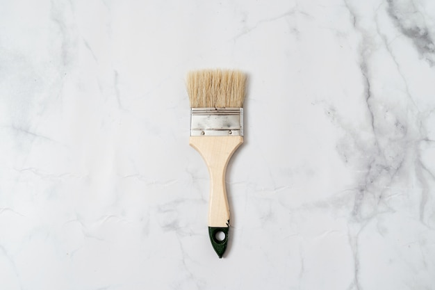 Paint tool brush top view on marble surface. minimal concept of renovation or crafts