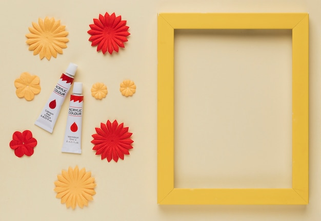 Paint tube; flower cutout and yellow wooden frame border on beige background