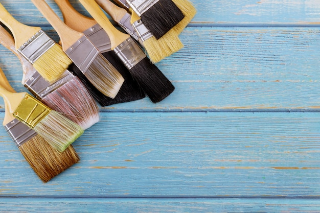 Paint various brush decorating supplies painting house renovation on blue wooden planks top view