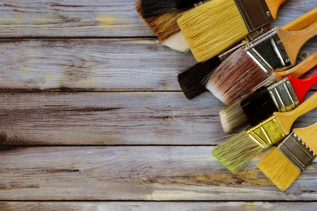 Нарисуйте различные кисти для отделочных работ покраска дома ремонт на синих деревянных досках вид сверху