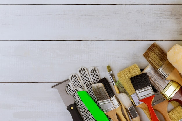 Paint various brush decorating supplies painting house renovation on wooden planks top view