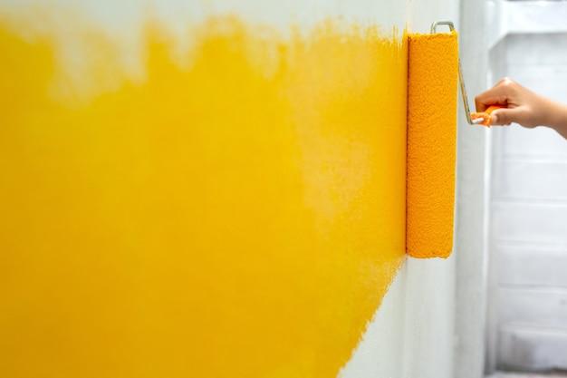壁にローラーで黄色を塗るdiy