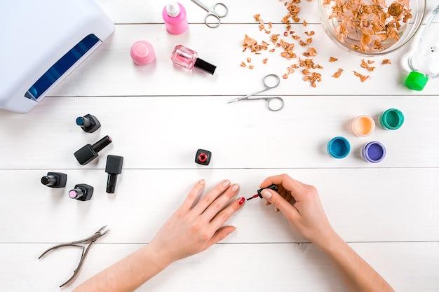 Нарисуйте ногти самостоятельно. маникюрный набор и лак для ногтей на деревянных фоне. вид сверху. скопируйте пространство. натюрморт. уход за ногтями.