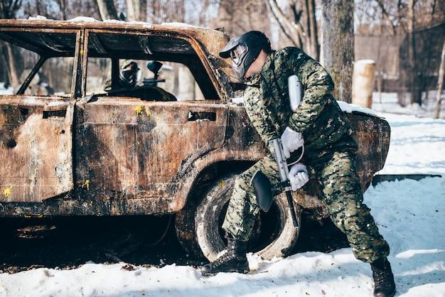 冬の森で燃やされた車の周りのペイントボールの戦い、ペイントボール。エクストリームスポーツ、ミリタリーゲーム