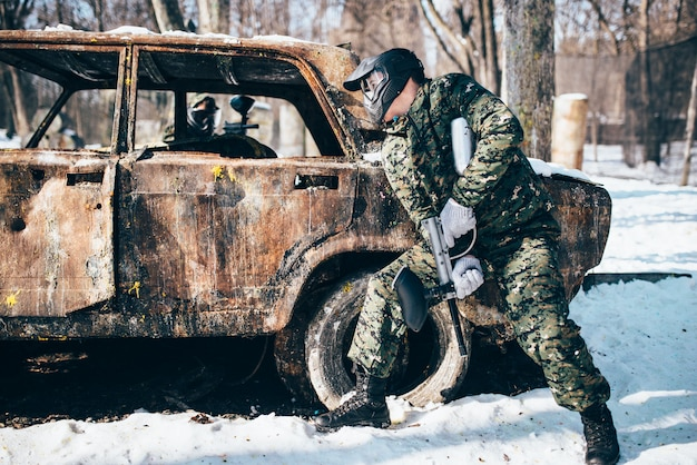 Paintball battle around burned car in winter forest, paintballing. extreme sport, military game