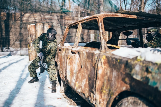 Paintball battle, burned car in winter forest