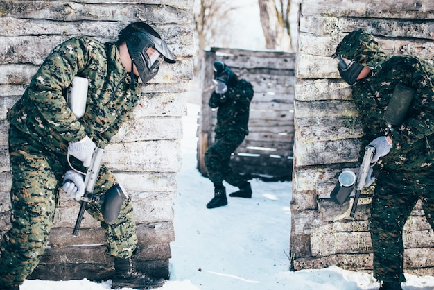 Paintball battle, paintballing, team shooting in winter forest. extreme sport, active military game