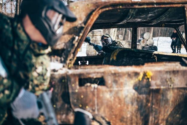 Пейнтбольный бой, игроки дерутся вокруг сгоревшей машины в зимнем лесу, пейнтбол. экстремальный спорт, военная игра