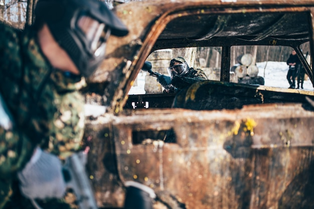 Paintball battle, players fight around burned car in winter forest, paintballing. extreme sport, military game
