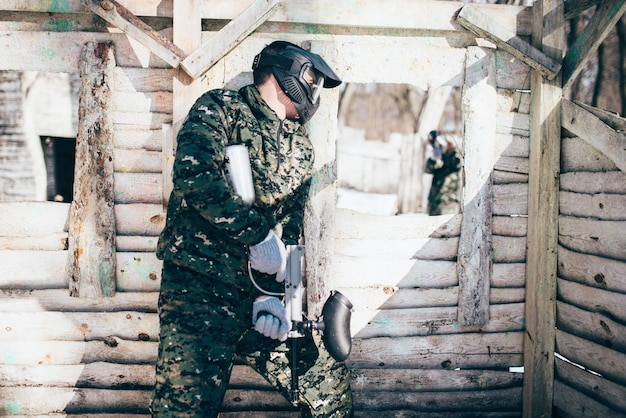 Paintball battle, skirmish in winter forest, paintballing. extreme sport, active military game