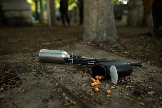 Пейнтбольный пистолет и маркерные шары на земле крупным планом