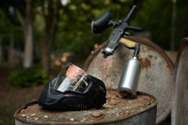 Пейнтбольный пистолет и защитная маска крупным планом