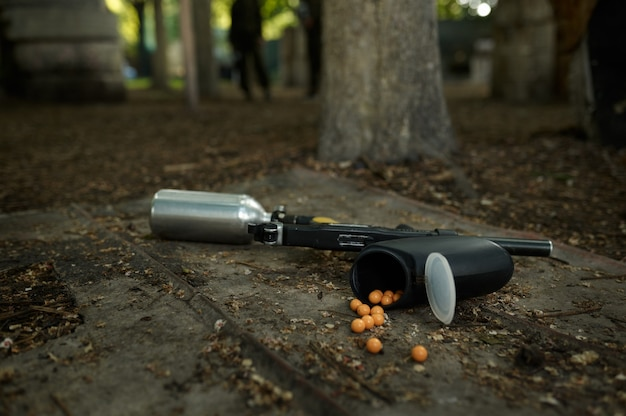 Paintball gun and marker balls on ground closeup