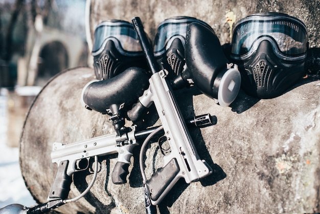 Paintball masks with protection glasses and marker guns, nobody. extreme game equipment, sport ammunition