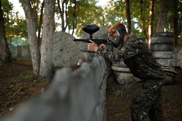 Пейнтболист, прицеливание с ружьями из приюта на детской площадке