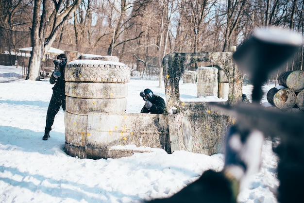 Paintball player hands with marker gun shooting at the enemy, winter forest battle. extreme sport game