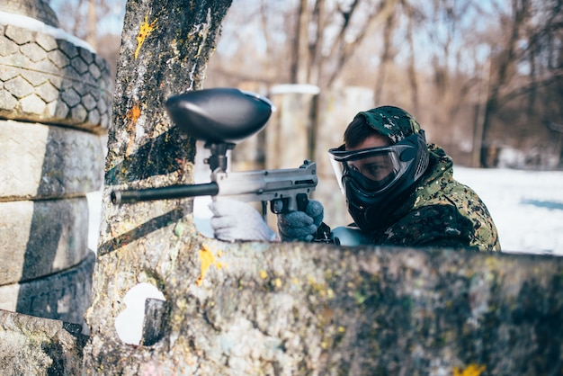Пейнтболист в защитной маске стреляет по врагу, вид сзади, зимний лесной бой, пейнтбол. экстремальная спортивная игра