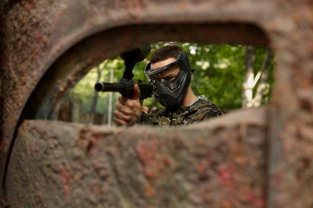 Игрок в пейнтбол в форме и маске в лесу